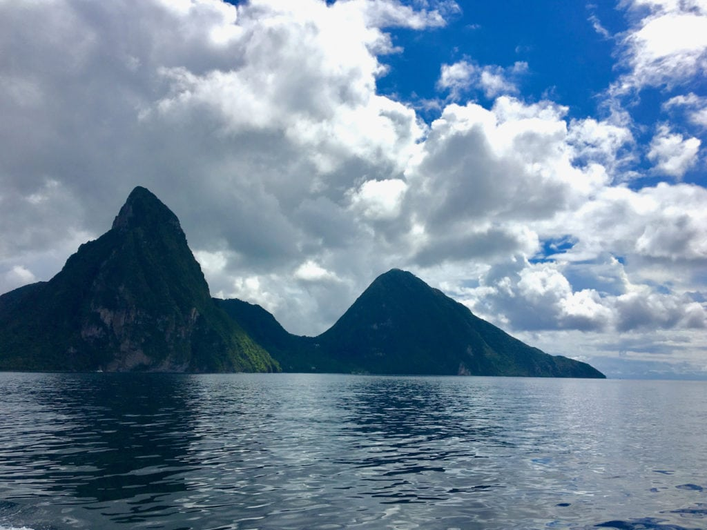 The Pitons rise dramatically off the coast of Saint Lucia, one of the greenest islands visited on the Southern Caribbean Cruise.