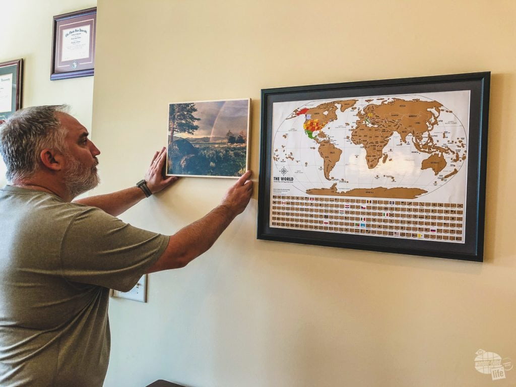 So, we got the Landmass Goods Travel Tracker Scratch Off map hung and now we are hanging one picture from every trip surrounding the map.