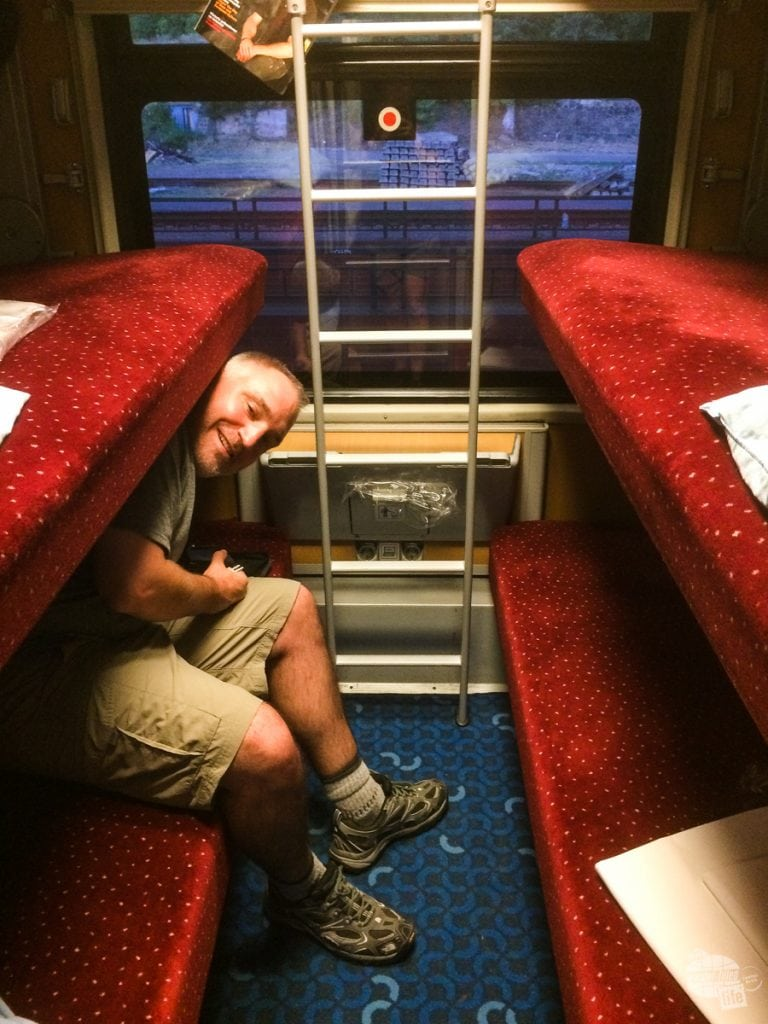 Grant getting into the bunk of the sleeper car.