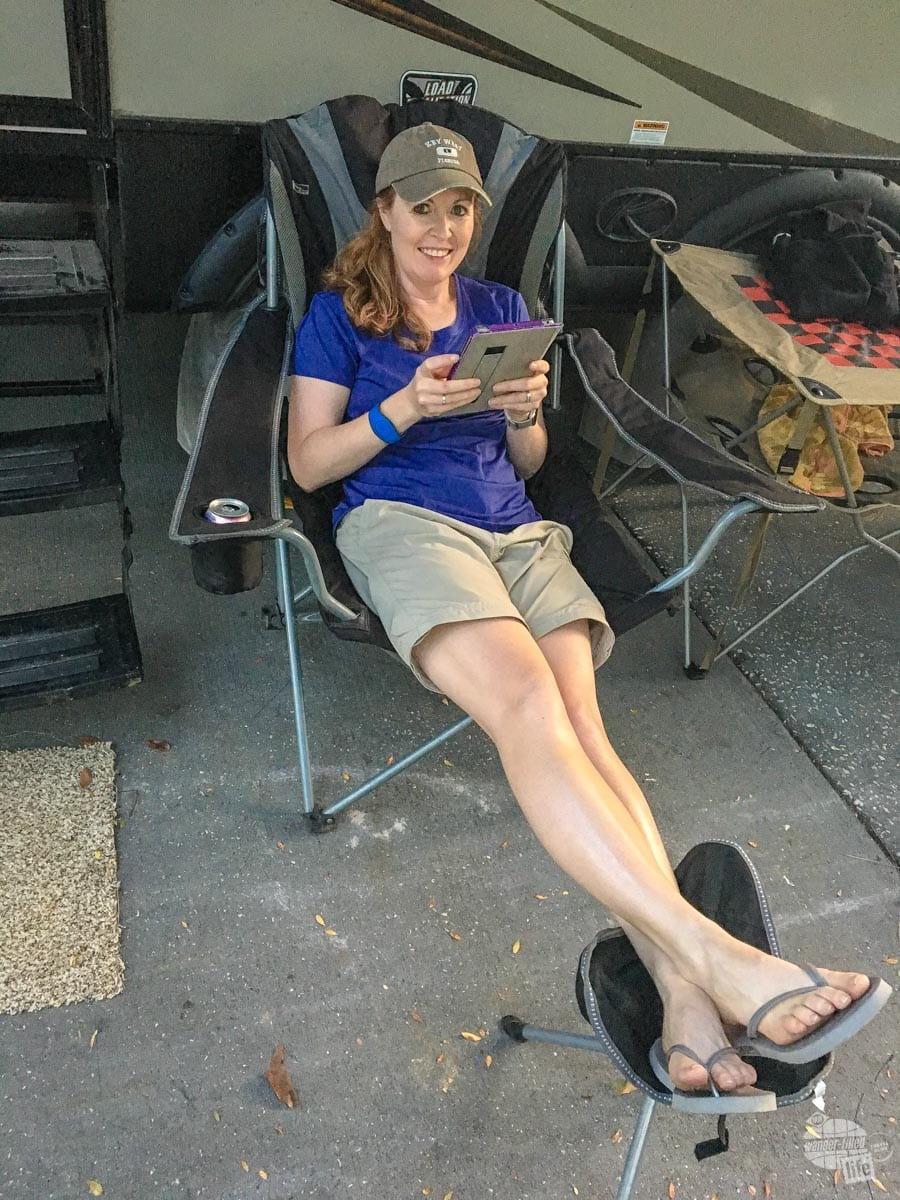 Bonnie reading a book on her iPad at the camper.