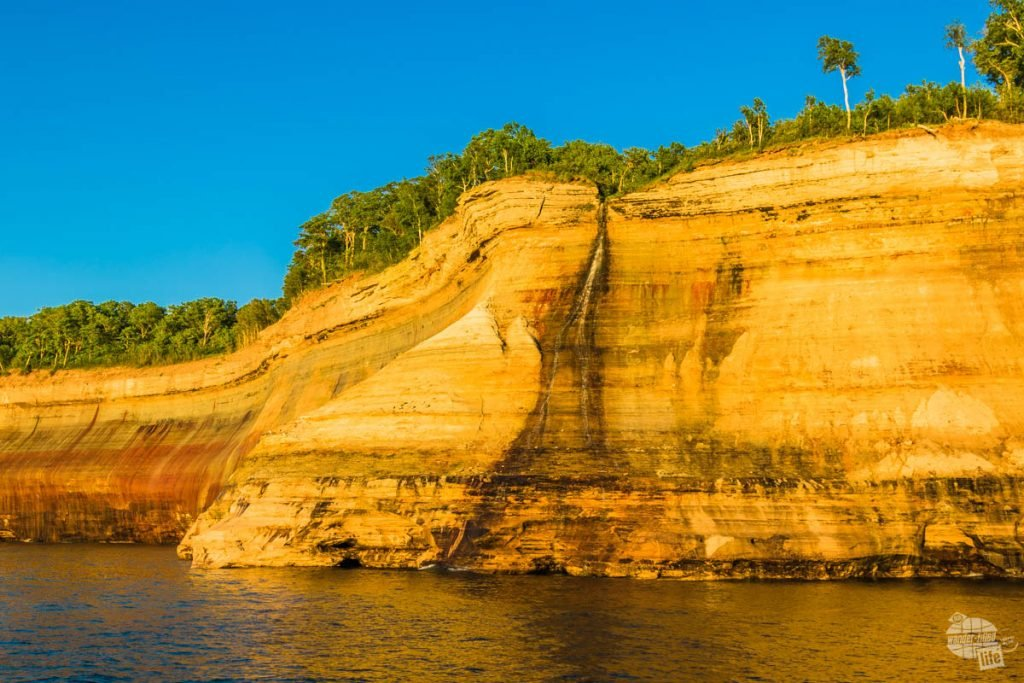 Bridal Veil Falls flows down the sandstone cliffs into Lake Superior at Pictured Rocks NL.
