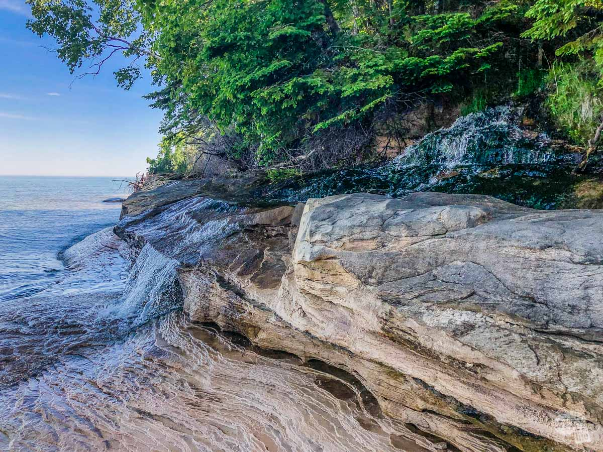 The almost hidden Elliot Falls, flowing right into Lake Superior.