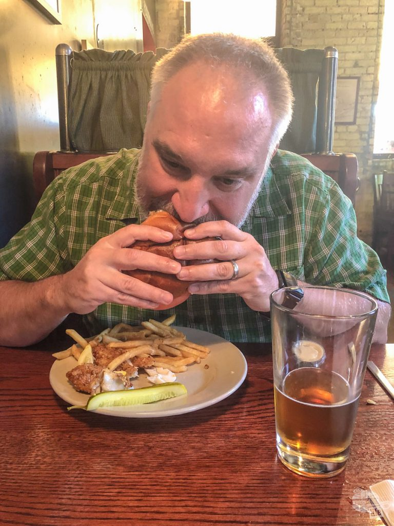 Grant biting into his first walleye sandwich at the Mackinaw Brewing Company.
