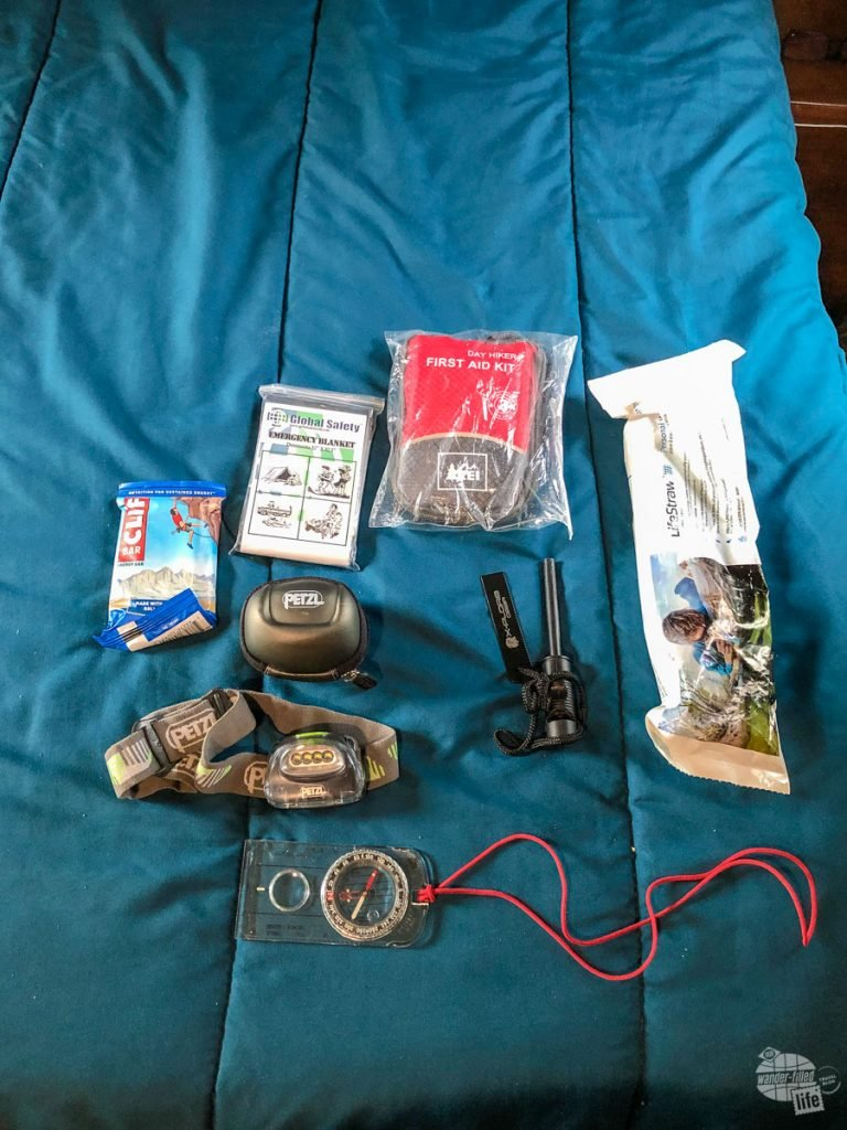 This is gear I always have in my pack: a space blanket, a first aid kit, a LifeStraw, a fire starter, a compass and a headlamp plus some extra food.