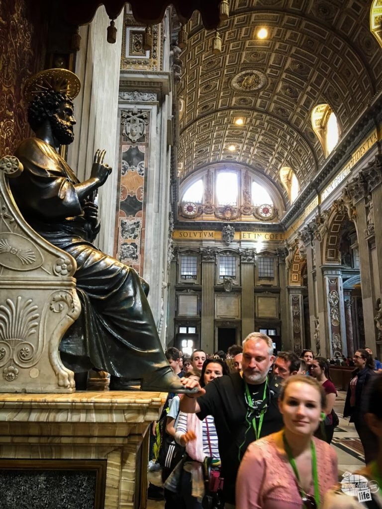 Grant rubbing the feet of St. Peter's statue in St. Peter's Basilica.