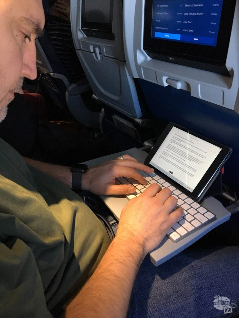 Grant working on a blog post on a flight. Using an iPad Mini and a Magic Keyboard in lieu of a laptop. It took us a while before we could save for a good laptop.