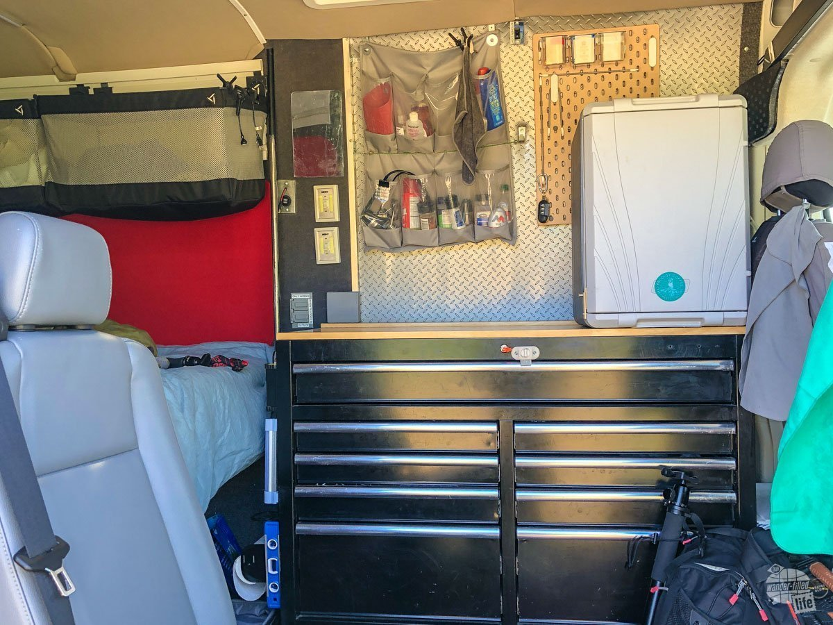 "The small ""kitchen"" of our camper van with a counter, drawer storage and a small refrigerator."