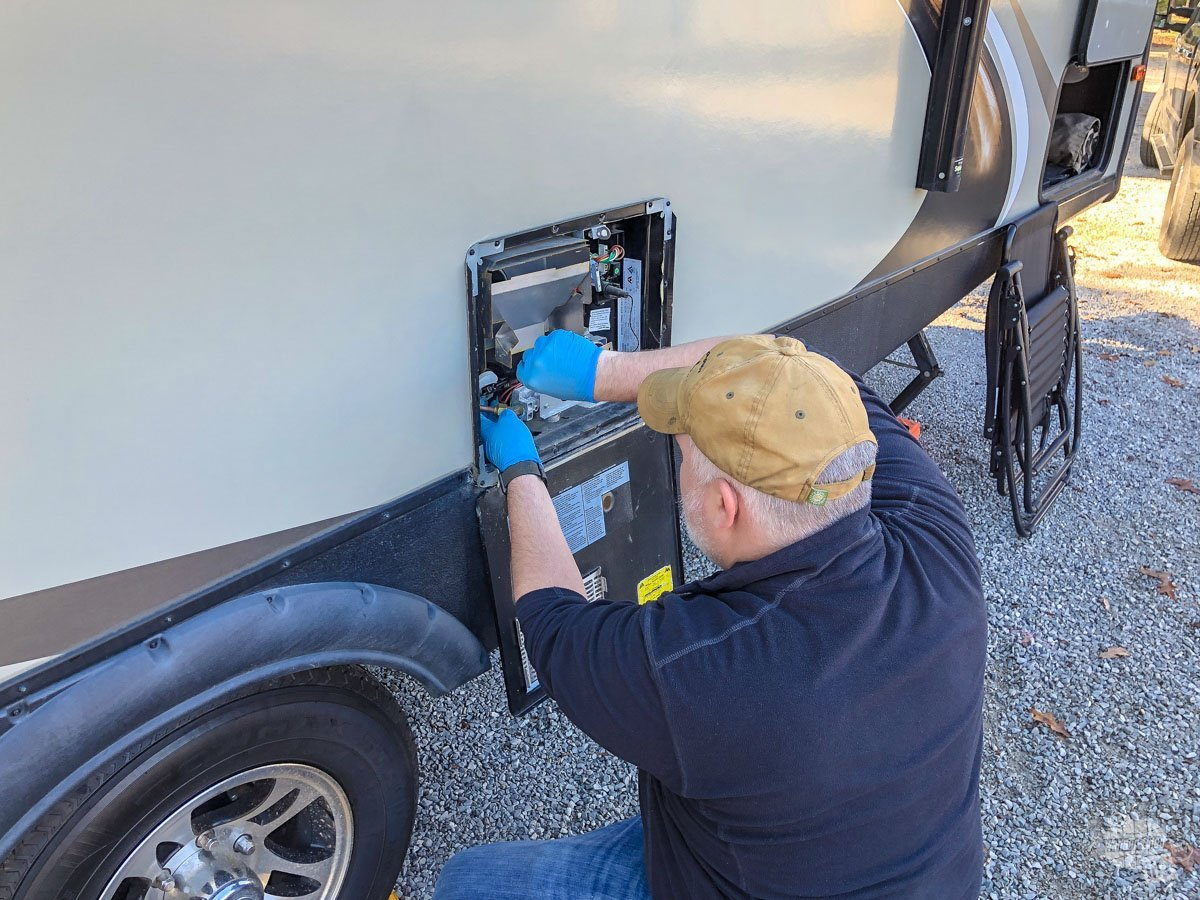 Grant working on draining the hot water tank while winterizing the camper.