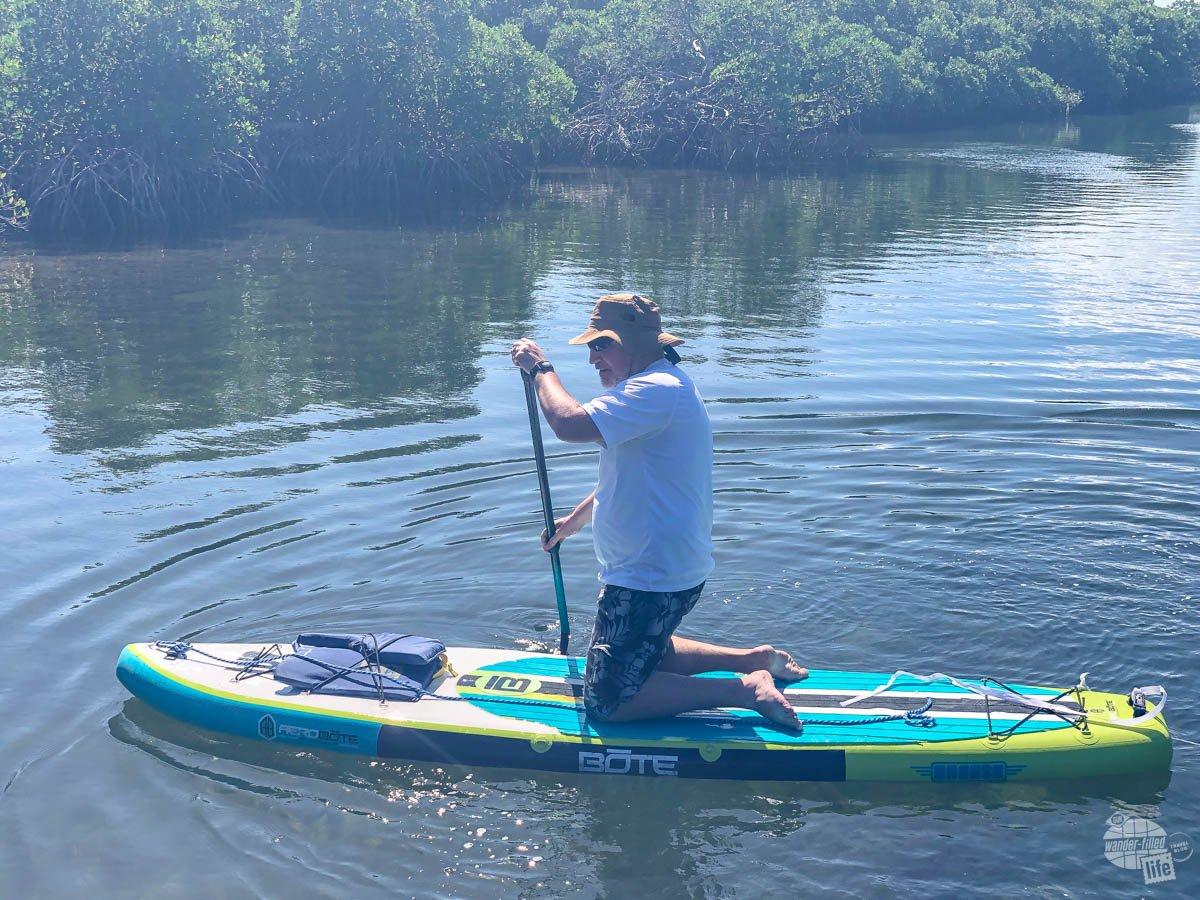 Grant kneels on a paddleboard at Biscayne National Park.