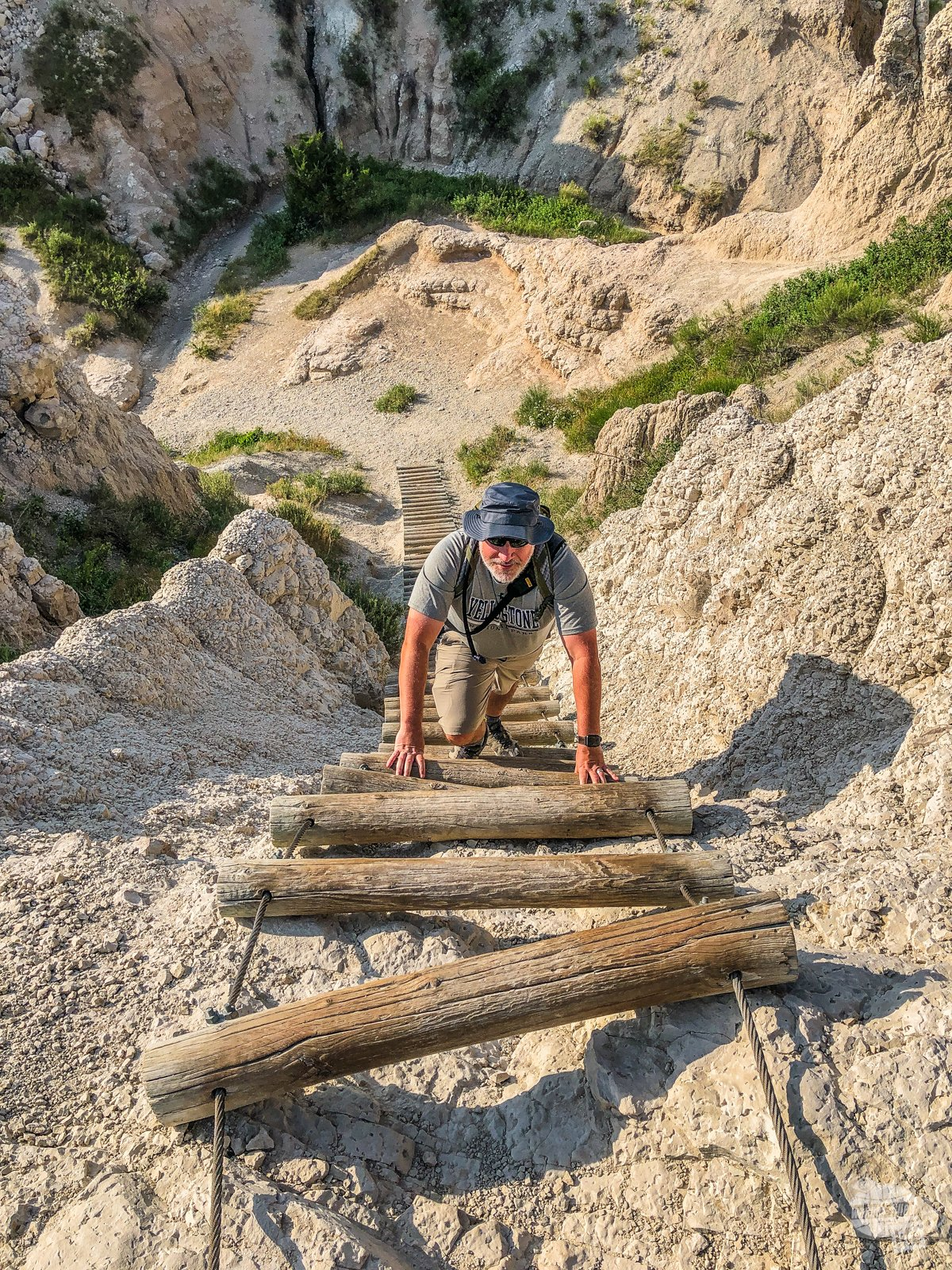 Grant climbing up a ladder made of logs on cable in Badlands National Park.