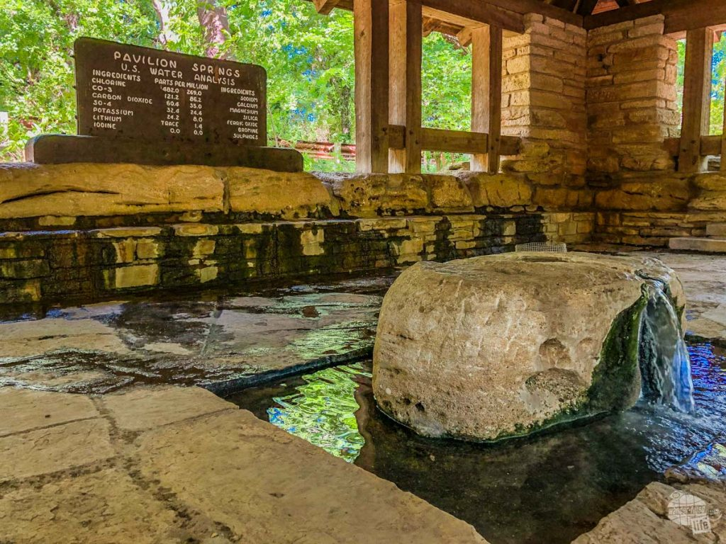 Pavilion Springs bubbling up in the foreground with a sign in the background detailing the mineral content of the water.