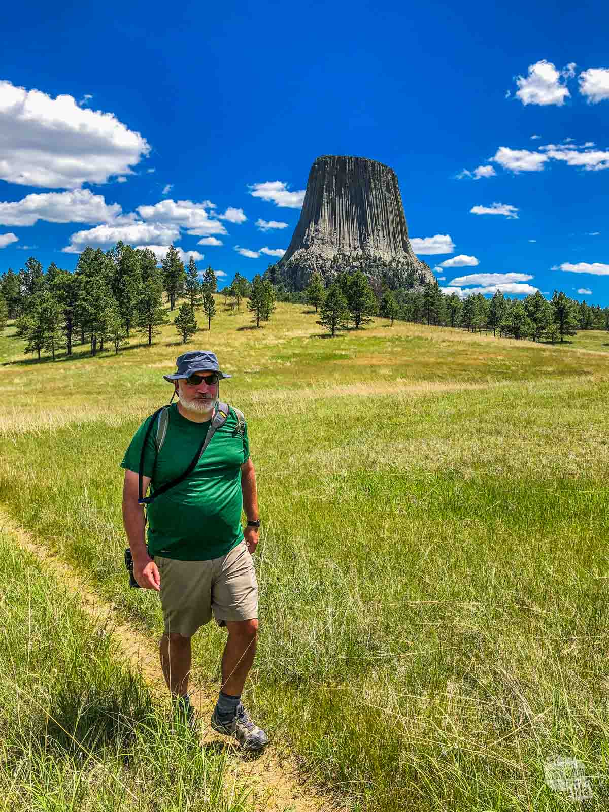 Grant hiking in the prairie with Devils Tower looming behind him.