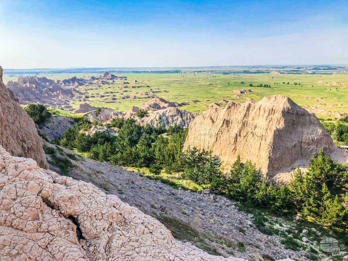 A wide view of green prairie and badlands stretching out to the horizon.