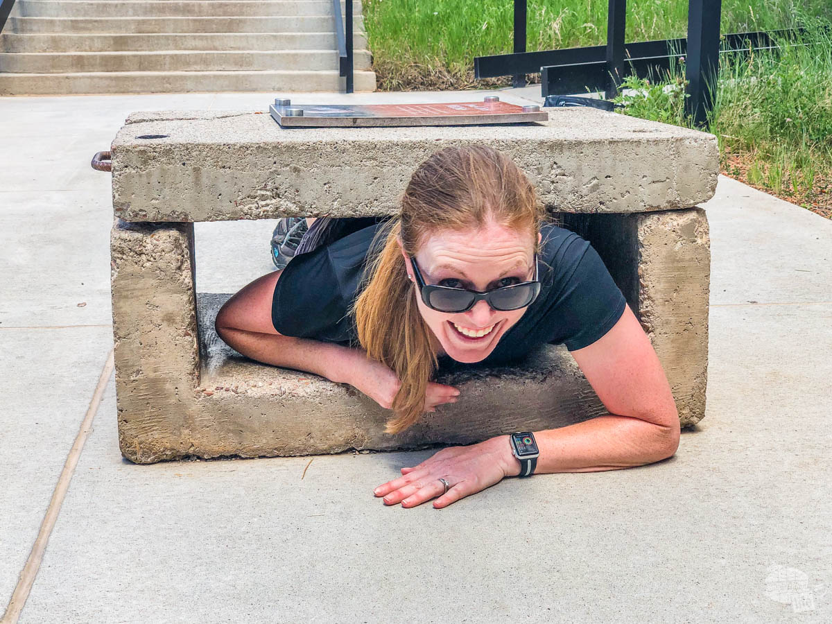 Bonnie Sinclair squeezing through the concrete test at Jewel Cave National Monument.