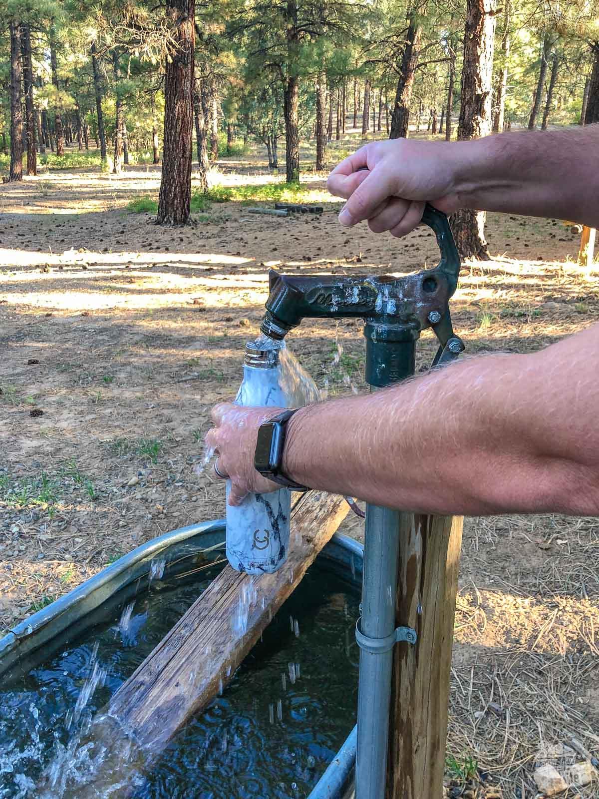 Filling up a Crazy Cap at a horse trough.